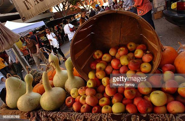 People walk by gourds left and a basket full of apples from Winrose Farm at the Farmer's Market Wednesday afternoon in Santa Monica It's some of the...