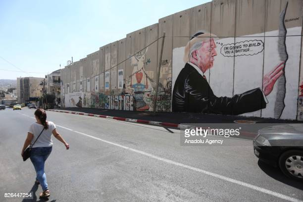 People walk by graffiti art depicting US President Donald J Trump on Israeli separation barrier in the West Bank town of Bethlehem on August 04 2017