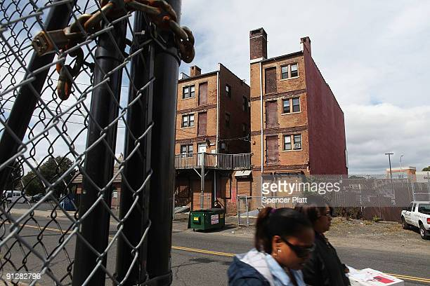 People walk by housing in a struggling section of town September 30 2009 in Bridgeport Connecticut According to statistics from the US Census Bureau...