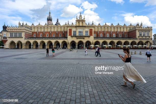 People walk by Krakow's UNESCO listed Main Square as lockdown measures have been eased on July 2 2020 in Krakow Poland Krakow one of the biggest...