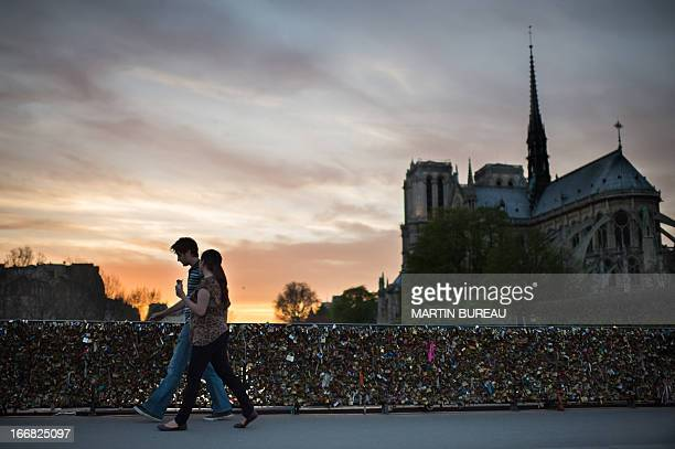 People walk by NotreDame Cathedral on April 17 2013 in Paris AFP PHOTO MARTIN BUREAU
