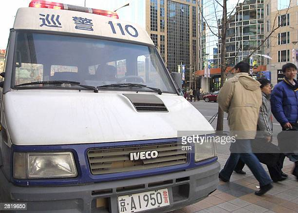 People walk by one of the many police vans produced in eastern China's Nanjing city by Iveco Italybased Fiat's trucking arm parked along a street in...