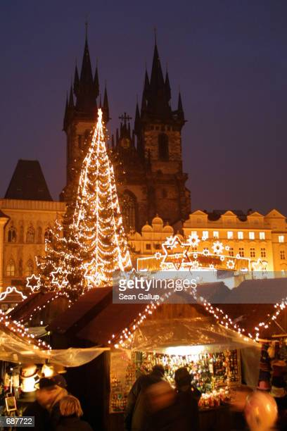 People walk by outdoor shops at the Christmas market on Pragues Old Town Square December 15 in the Czech Republic Christmas which was tolerated but...