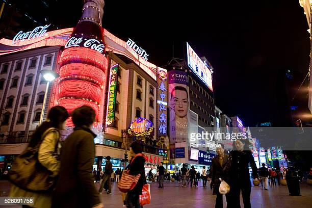 People walk by shops and restaurants with neon lights on Nanjing Road in People's Square in Shanghai, China.
