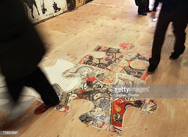People walk by street art on the floor at the Wooster on Spring street art exhibit December 15 2006 at 11 Spring Street in New York City Over 50...