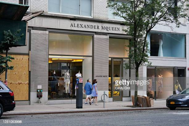 People walk by the Alexander McQueen store on Madison Avenue as the city moves into phase two re-opening from the coronavirus pandemic on June 20,...