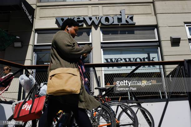 People walk by the co-working space WeWork in the Williamsburg neighborhood in Brooklyn on March 26, 2019 in New York City. WeWork, which lets...
