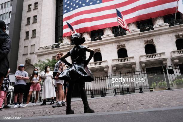 People walk by the Fearless Girl statue outside of the New York Stock Exchange on August 10, 2021 in New York City. Markets were up in morning...