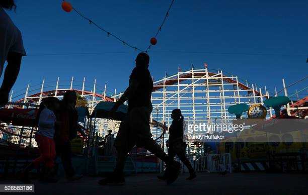 People walk by the Giant Dipper roller coaster at Belmont Park along Mission Beach in San Diego CA on Monday October 27 2014