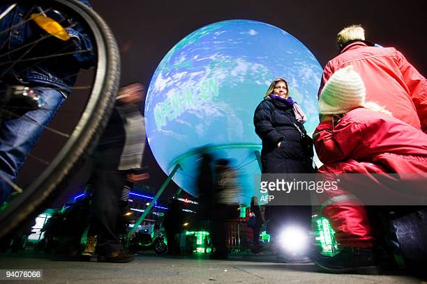 People walk by the gigantic earth globe on the town square in Copenhagen on December 6 on the eve of the opening of the United Nations Climate...