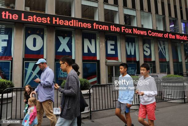 People walk by the headquarters of 21st Century Fox on June 13 2018 in New York City Comcast the giant cable operator on Wednesday officially made a...