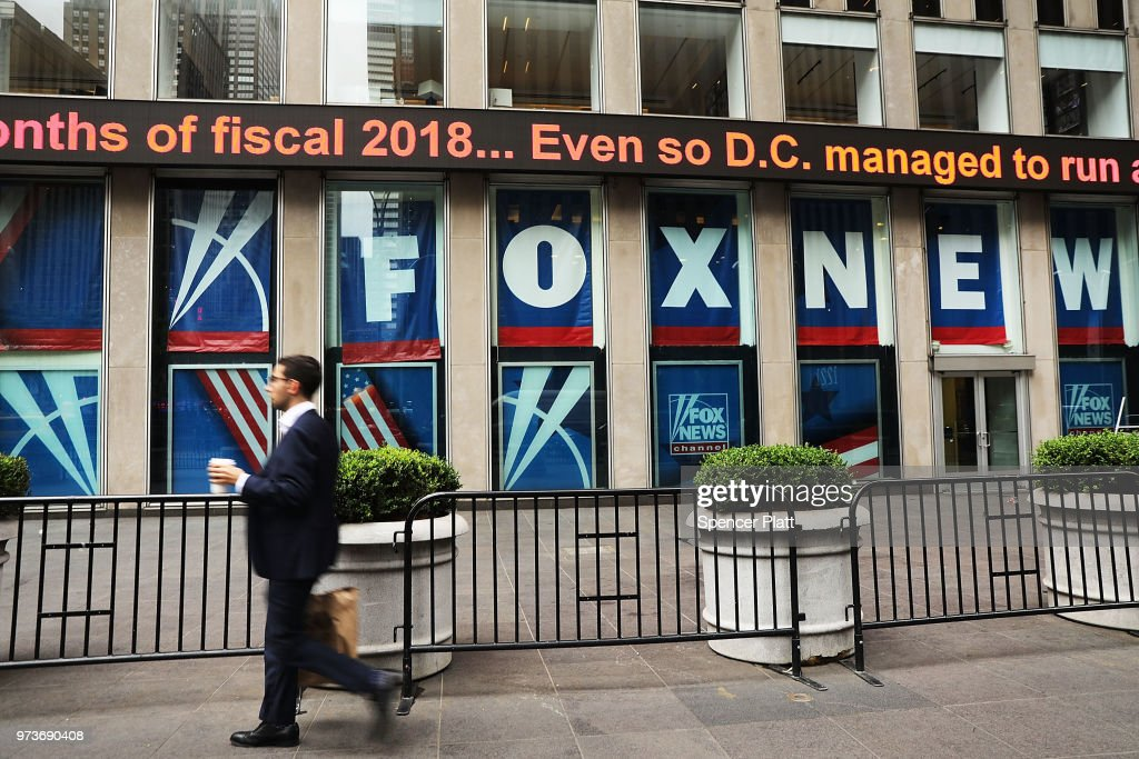 People walk by the headquarters of 21st Century Fox on June 13, 2018 in New York City. Comcast, the giant cable operator, on Wednesday officially made a $65 billion all-cash bid for the majority of Fox.