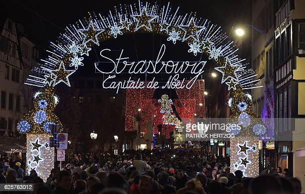People walk by the illuminated entrance of the the Christmas market in Strasbourg during the opening day in Strasbourg eastern France on November 25...