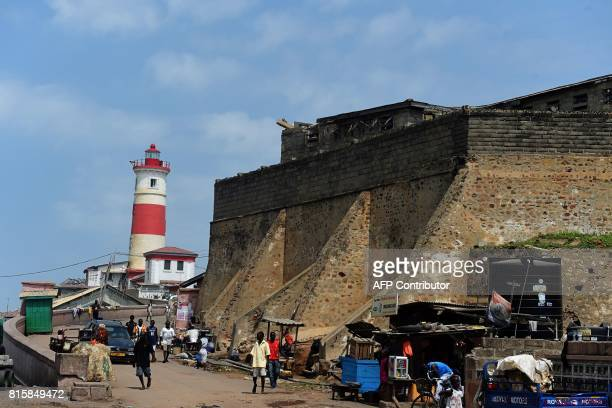 People walk by the Jamestown Lighthouse and the James Fort Prison built by the British as a trading post and prison in the Jamestown district central...
