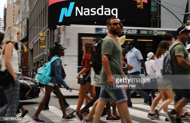 People walk by the Nasdaq MarketSite in Times Square on July 30, 2018 in New York City. As technology stocks continued their slide on Monday, the...