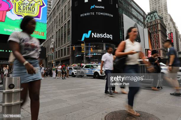 People walk by the Nasdaq MarketSite in Times Square on July 30 2018 in New York City As technology stocks continued their slide on Monday the Nasdaq...