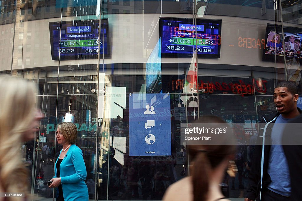 People walk by the Nasdaq stock market where a television monitor displays the newly debuted Facebook stock price at the end of the trading day on May 18, 2012 in New York, United States. The social network site began trading after 11:30 a.m. with shares jumping 13% to $43 before quickly falling. Facebook ended the day at $38.23, a fraction above its initial public offering price.