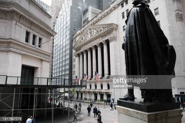 People walk by the New York Stock Exchange after global stocks fell as concerns mount that rising inflation will prompt central banks to tighten...