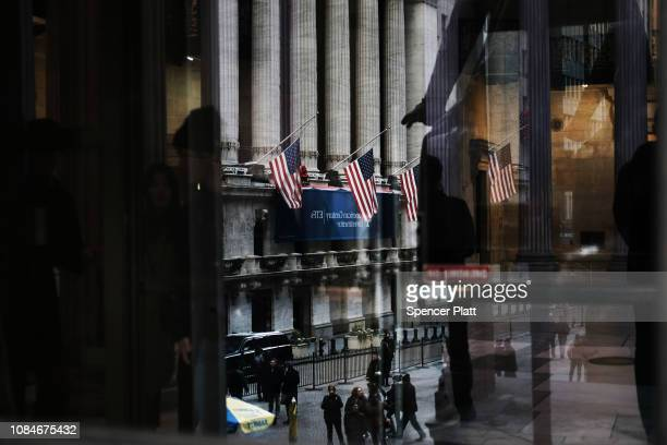 People walk by the New York Stock Exchange as the Federal Reserve Board Chairman Jerome Powell holds a news conference on December 19, 2018 in New...