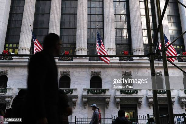 People walk by the New York Stock Exchange during the beginning of the Christmas holiday week on December 23 2019 in New York City Following news...