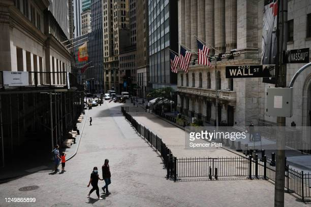 People walk by the New York Stock Exchange in an empty Financial District on June 15, 2020 in New York City. Markets gained ground in afternoon...