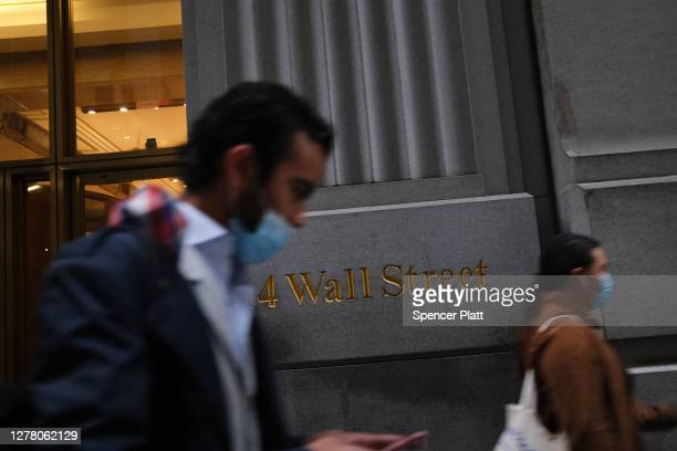 People walk by the New York Stock Exchange in lower Manhattan on October 02, 2020 in New York City. Stocks and markets around the world have fallen...