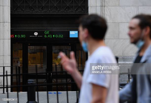 People walk by the New York Stock Exchange in lower Manhattan on October 5, 2020 in New York City. - Stock markets bounced back on reports suggesting...