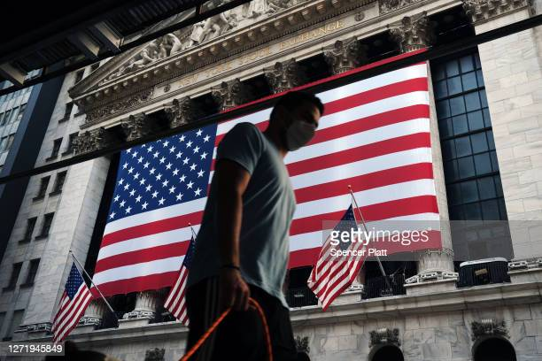 People walk by the New York Stock Exchange near One World Trade Center, the Freedom Tower, in lower Manhattan during commemoration ceremonies for the...