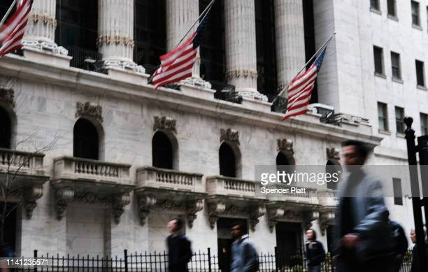 People walk by the New York Stock Exchange on April 08 2019 in New York City Markets are reacting as President Trump considers placing Herman Cain a...