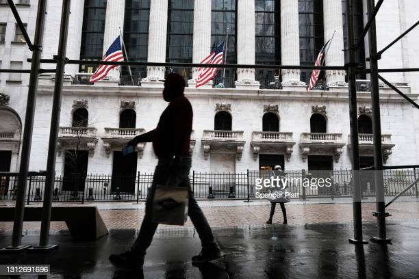 People walk by the New York Stock Exchange on April 15, 2021 in New York City. After major companies reported strong earnings and new economic data...