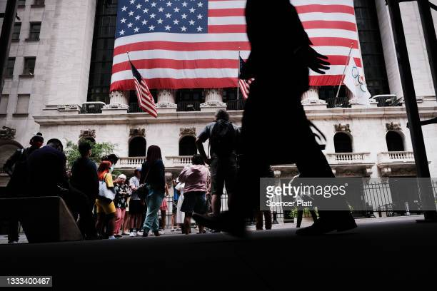 People walk by the New York Stock Exchange on August 10, 2021 in New York City. Markets were up in morning trading as investors look to a rare...