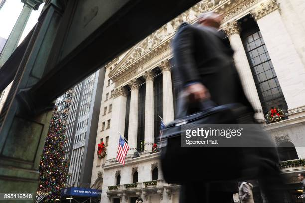 People walk by the New York Stock Exchange on December 19 2017 in New York City The Dow Jones industrial average rose in morning trading as lawmakers...