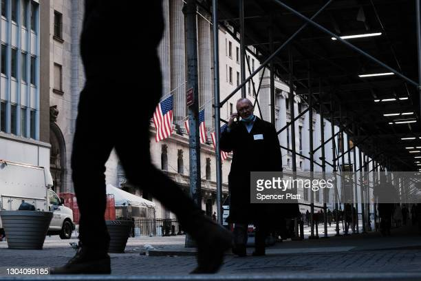 People walk by the New York Stock Exchange on February 25, 2021 in New York City. As a rapid rise in Treasury yields has made equity investors...