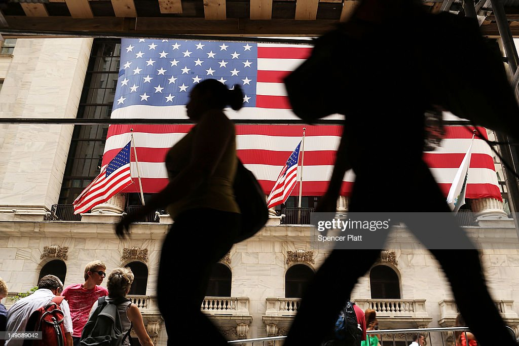 People walk by the New York Stock Exchange on July 31, 2012 in New York City. As meetings by the U.S. and European central bankers continue, investors have been cautious as they await an outcome of the talks as early as Wednesday.The Dow Jones Industrial Average slipped 64 points, or 0.5%.