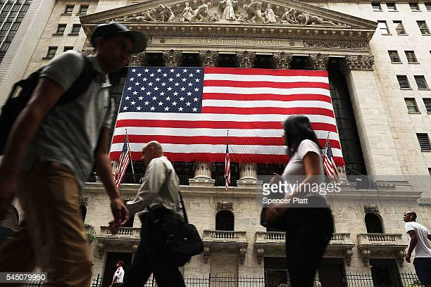 People walk by the New York Stock Exchange on July 5 2016 in New York City Markets were down in morning trading as investors are still nervous over...