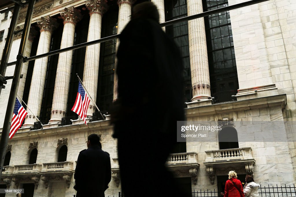 People walk by the New York Stock Exchange on March 28, 2013 in New York City. The S&P 500 finished at an all time high, gaining 6 points, or 0.4%, to end at a record close of 1569.19.