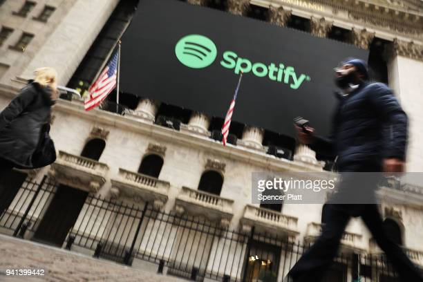 People walk by the New York Stock Exchange on the morning that the music streaming service Spotify begins trading shares at the NYSE on April 3 2018...