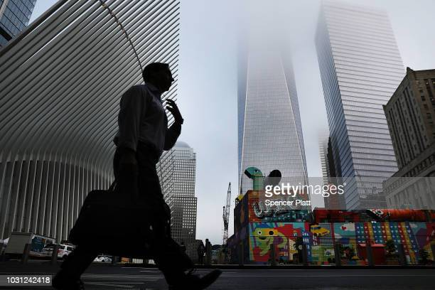 People walk by the Oculus located at the World Trade Center before the start of a morning commemoration ceremony for the victims of the terrorist...