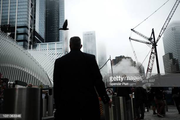 People walk by the Oculus located at the World Trade Center during a morning commemoration ceremony for the victims of the terrorist attacks...