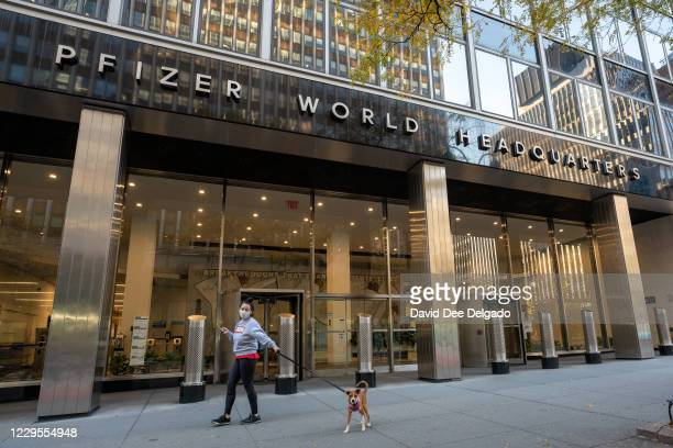 People walk by the Pfizer headquarters on November 9, 2020 in New York City. Pharmaceutical company Pfizer announced positive early results on its...