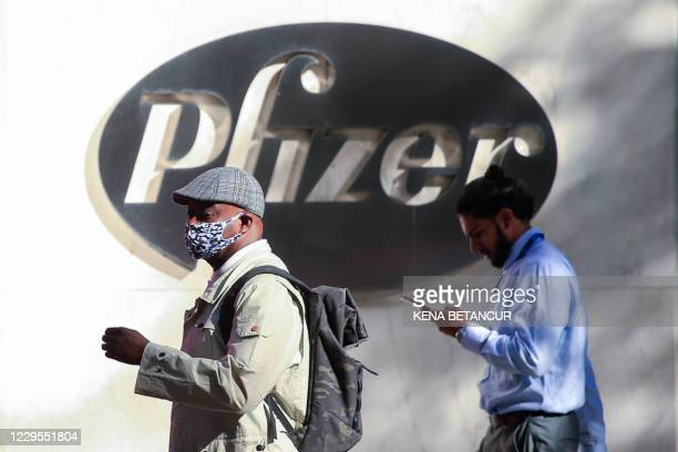 People walk by the Pfizer world headquarters in New York on November 9, 2020. - Pfizer stock surged higher on November 9, 2020 prior to the opening...