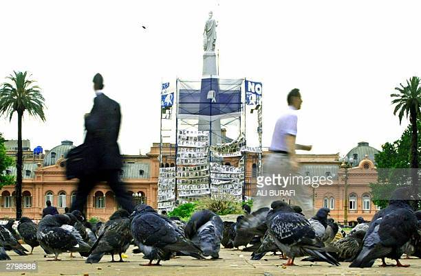 People walk by the Plaza de Mayo square in downtown Buenos Aires nearby hundreds of photographs of missing people during the military dictatorship 10...