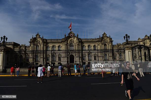 People walk by the Presidential Palace in Lima's historic centre during the AsiaPacific Economic Cooperation Summit on November 17 2016 Top world...