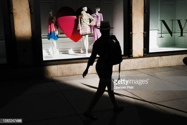 People walk by the recently reopened Saks Fifth Avenue retail store in Manhattan as the city enters Phase 2 of reopening following restrictions...