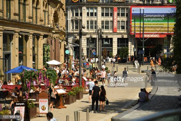 People walk by the restaurants and cafes near The Printworks in the centre of Manchester, northwest England, on July 31, 2020. - Britain on Friday...