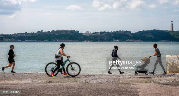 People walk by the Tagus River in the Cais do Sodré on April 25 2020 in Lisbon Portugal Few people take to the streets due to the COVID19 Coronavirus...