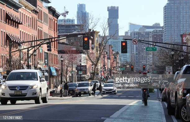 People walk cycle and drive along Washington Street the main retail street on March 15 2020 in Hoboken New Jersey The municipal government in Hoboken...