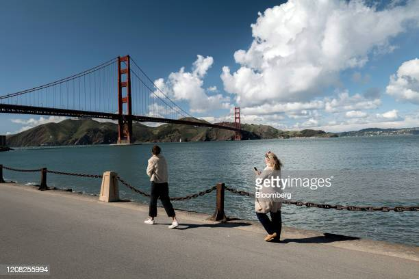 People walk distanced from each other in front of the Golden Gate Bridge at Crissy Field in San Francisco, California, U.S., on Wednesday, March 25,...