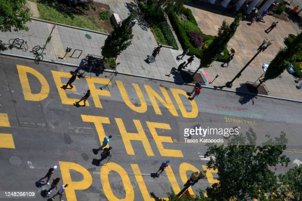 """People walk down 16th street after """"Defund The Police"""" was painted on the street near the White House on June 08, 2020 in Washington, DC. After days..."""