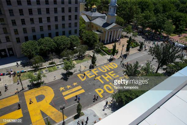 """People walk down 16th street after """"Defund The Police"""" was painted on the street near the White House on June 08 2020 in Washington DC After days of..."""